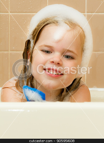 My toy and the tub. stock photo, Young girl playing with a random toy in the bathtub while covered in suds by txking