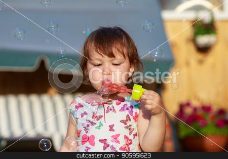 Cute little girl is blowing a soap bubbles stock photo, Cute little girl is blowing a soap bubbles. by Alfira Poyarkova
