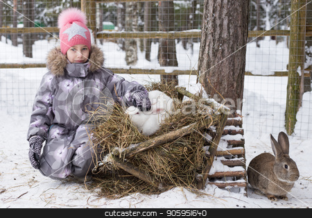 A cute little girl in a pink cap playing with a white rabbit stock photo, A cute little girl in a pink cap playing with a white rabbit in the winter city park. by Alfira Poyarkova