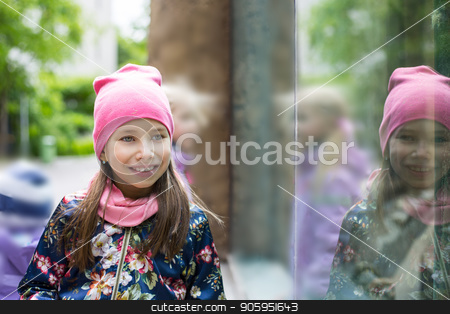 Beautiful kid girl with long hair in rose cap smiling outdoors.