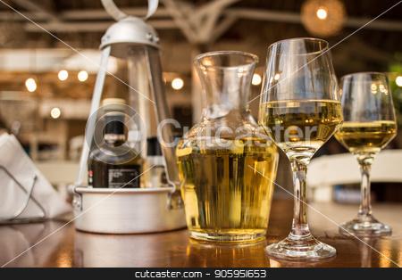 Pouring white wine into the glass against wooden table stock photo, Pouring white wine into the glass against wooden table. Romantic dinner. by Alfira Poyarkova