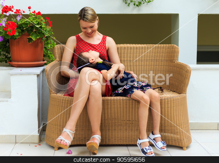 Mother and young daughter are sitting in a rattan chair of a Mediterranean hotel stock photo, Mother and young daughter are sitting in a rattan chair of a Mediterranean hotel. by Alfira Poyarkova