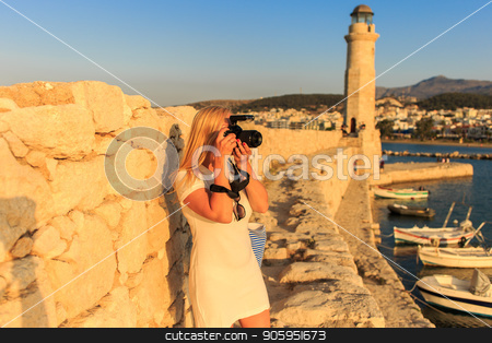 Traveler woman photographer with professional camera takes shot of Rethymno,Crete, Greece. stock photo, Traveler woman photographer with professional camera takes shot of Rethymno,Crete, Greece. Caucasian female photographing outdoors. Europe travel concept. by Alfira Poyarkova