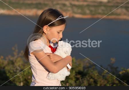 Child girl is embracing soft toy bear. stock photo, Child girl is embracing soft toy bear. Friendship concept. by Alfira Poyarkova