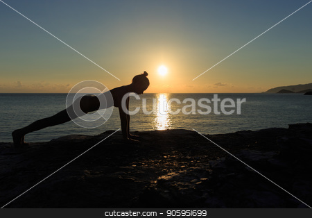 Young female silhouette doing plank exercise on a beach at sunrise stock photo, Young female silhouette doing plank exercise on a beach at sunrise. by Alfira Poyarkova