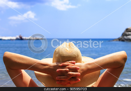 Travel, vocation, holiday concept. Woman in hat is lying on deckchair on beach by sea. stock photo, Travel, vocation, holiday concept. Woman in hat is lying on deckchair on beach by sea. Girl on summer holidays vacation. Hands behind head. by Alfira Poyarkova