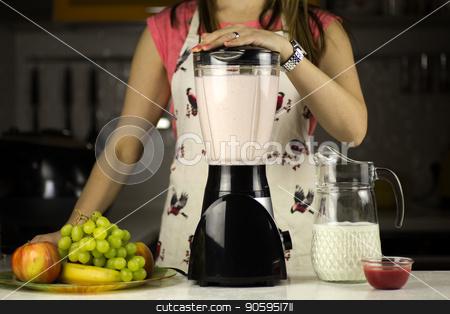 woman preparing a milk cocktail stock photo, A beautiful woman preparing a milk cocktail with fruits in the kitchen. by Alfira Poyarkova