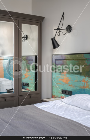 Stylish hotel room stock photo, Nice room in a hotel with light walls. There is a bed with a colorful wooden bedhead, white linens with a coverlet on the bed, nightstand, black lamp on the wall, dark gray wardrobe with a mirror. by bezikus