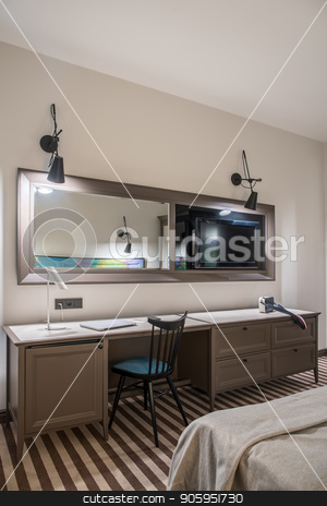 Stylish hotel room stock photo, Hotel room with light walls and a striped floor. There is a wide table with drawers, chair, bed, mirror, TV, luminous lamps. On the table there is a laptop and a shoulder bag. Vertical. by bezikus