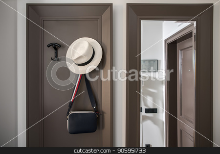 Stylish hotel room stock photo, Contemporary hallway in a hotel room with light walls. There is a full length mirror, hangers with a hanging shoulder bag and a hat. Horizontal. by bezikus