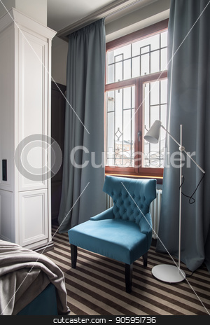 Stylish hotel room stock photo, Wonderful hotel room with light walls and a striped floor. There is a big window with curtains, blue armchair, white floor lamp and a blue bed with a gray coverlet. Vertical. by bezikus