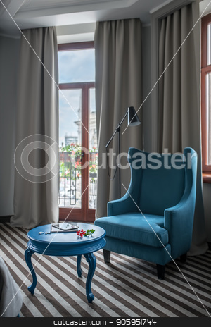 Stylish hotel room stock photo, Bright hotel room with light walls and a striped floor. There is a round blue table with an armchair, window with curtains, glass door to the balcony, dark floor lamp. Vertical. by bezikus