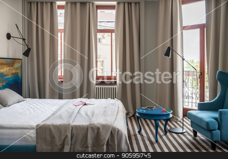 Stylish hotel room stock photo, Trendy hotel room with light walls and a striped floor. There is a double bed with a colorful wooden bedhead, round blue table with an armchair, windows with curtains, door to the balcony, floor lamp. by bezikus
