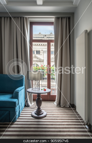 Stylish hotel room stock photo, Modern hotel room with light walls and a striped floor. There is a blue sofa, small round table with a lamp with a lampshade, glass door to the balcony with curtains, white long radiator on the wall. by bezikus