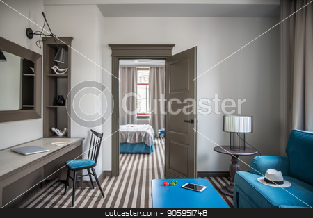 Stylish hotel room stock photo, Light hotel room with a striped floor. There is a blue armchair with a hat, different tables, lamps, chair, shelves with decorations, mirror on the wall, door, bed, windows with curtains. Horizontal. by bezikus
