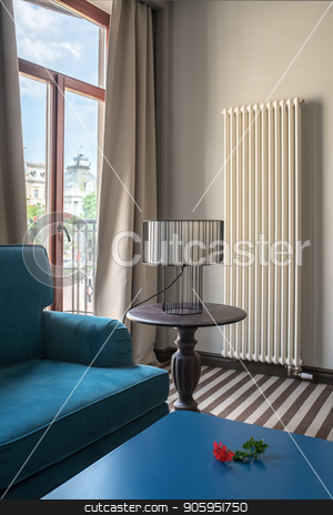 Stylish hotel room stock photo, Elegant hotel room with light walls and a striped floor. There is a blue sofa with a same table, wooden round table with a lamp with a lampshade, glass door to the balcony with curtains, radiator. by bezikus