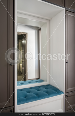 Stylish hotel room stock photo, Beautiful hotel room with a brown lockers and a white niche with a soft blue seat and a mirror. Door to the bathroom is reflected in the mirror. Closeup horizontal photo. by bezikus