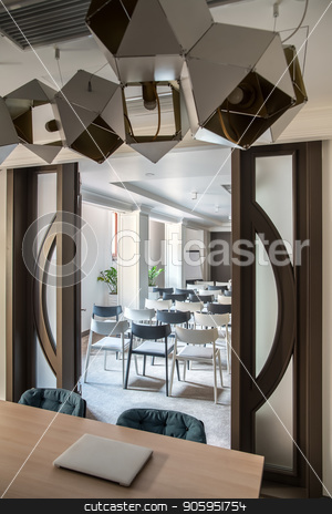 Modern conference hall stock photo, Large conference hall with white walls and a gray floor. There are many light and dark chairs, board, wooden table with a laptop, wide door, columns, hanging fancy lamps, plants in the pots. Vertical. by bezikus