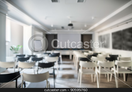 Modern conference hall stock photo, Blurred photo of a conference hall with white walls and a gray floor. There are many light and dark chairs, board, projector, tables, lamps, plant in a pot. Horizontal. by bezikus