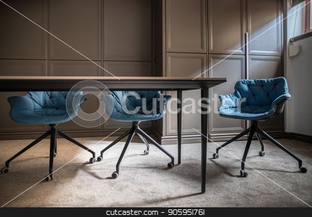 Modern meeting room stock photo, Empty meeting room with a gray carpet on the floor. There is a wooden table with three blue soft chairs, lockers and a window with a curtain. Horizontal. by bezikus