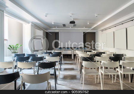 Modern conference hall stock photo, Light conference hall with white walls and a gray floor. There are many light and dark chairs, board, projector, tables with soft chairs, lamps, plant in a pot. Horizontal. by bezikus