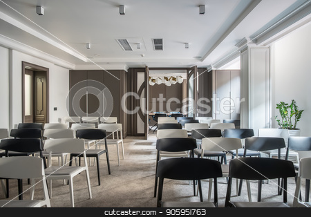 Modern conference hall stock photo, Stylish conference hall with white walls and a gray floor. There are many light and dark chairs, table with soft chairs, lamps, plant in a pot, doors, lockers, columns. Horizontal. by bezikus