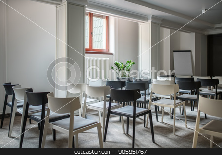 Big conference hall stock photo, Modern conference hall with white walls and a gray floor. There are many light and dark chairs, board, lamps, plant in a pot, window, radiator. Horizontal. by bezikus