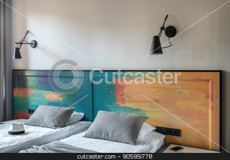 Stylish hotel room stock photo, Nice room in a hotel with light walls. There are two beds with a colorful wooden bedhead, black lamps on the wall, curtain, nightstand with a smartphone. Horizontal. by bezikus