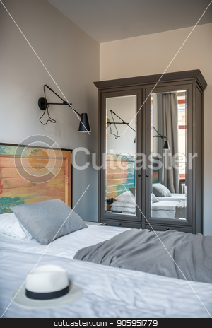 Stylish hotel room stock photo, Comfortable room in a hotel with light walls. There are two beds with a colorful wooden bedhead, black lamps on the wall, window with curtains, nightstand, dark gray wardrobe with mirrors. Vertical. by bezikus