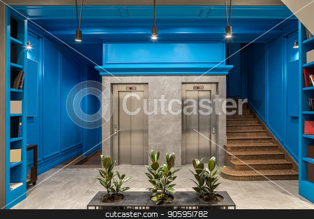 Stylish interior in hotel stock photo, Illuminated hallway in the hotel with blue walls and a tiled gray floor. There are two lifts, brown stair, shelves with books, black stand with green plants in the pots, hanging lamps. Horizontal. by bezikus