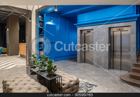 Stylish interior in hotel stock photo, Amazing hallway in the hotel with blue walls and a tiled floor. There are two lifts, brown stair, shelves with books, black stand with green plants in the pots, sofas, luminous lamps, reception desk. by bezikus