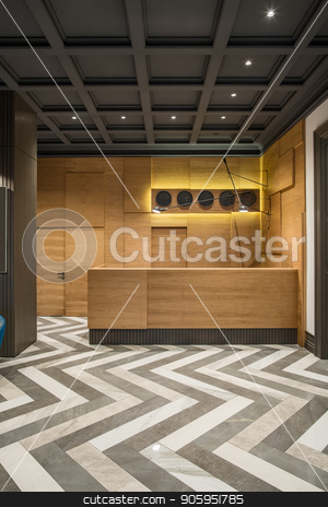 Stylish interior in hotel stock photo, Interior with luminous lamps in the hotel with dark ceiling and patterned tiled floor. There is a wooden reception with several black clocks and hanging lamps, door, column. Vertical. by bezikus