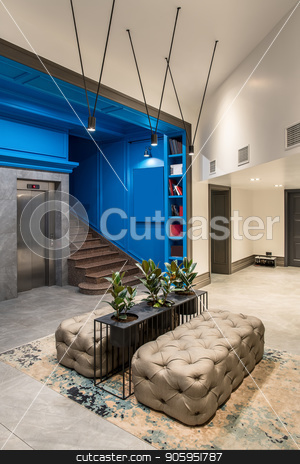 Stylish interior in hotel stock photo, Modern hallway in the hotel with blue and light walls and a tiled floor. There is a lift, brown stair, shelves with books, black stand with green plants in the pots, sofas, luminous lamps, doors. by bezikus
