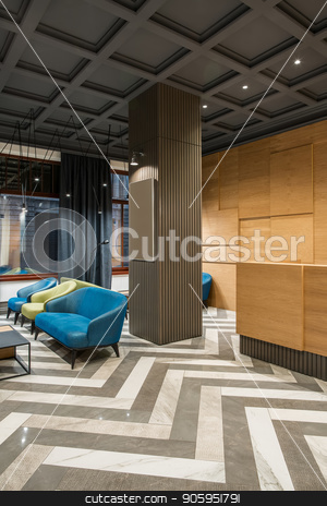Stylish interior in hotel stock photo, Fine interior with luminous lamps in the hotel with dark ceiling and patterned tiled floor. There is a wooden reception, column, multicolored armchairs and sofas, tables, windows with curtains. by bezikus