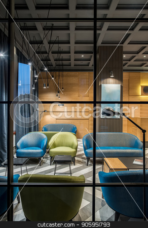 Stylish interior in hotel stock photo, Illuminated interior in the hotel with dark ceiling and patterned tiled floor. There is a wooden reception, column, multicolored armchairs and sofas, tables, different lamps, windows with curtains. by bezikus