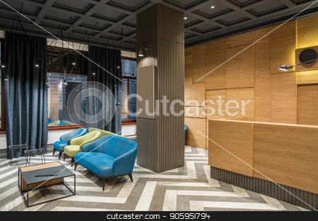 Stylish interior in hotel stock photo, Nice interior with luminous lamps in the hotel with dark ceiling and patterned tiled floor. There is a wooden reception with black clock and a hanging lamp, column, multicolored armchairs, tables. by bezikus