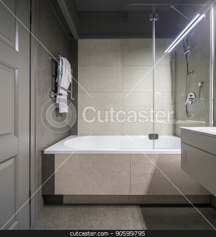 Stylish bathroom in hotel stock photo, Stylish bathroom with light tiled walls. There is a white bath with a shower and a glass partition, chrome towel rack, sink, gray door, luminous lamps. Vertical. by bezikus
