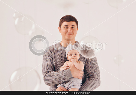 portrait: happy dad holds a child in a knitted hat in his hands. Family in warm grey clothes on white background stock photo, portrait: happy dad holds a child in a knitted hat in his hands. Family in warm grey clothes on white background by aaalll3110