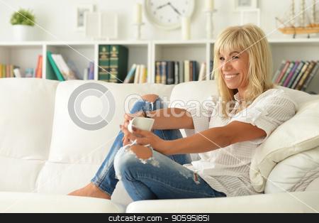 beautiful woman with a cup of tea on sofa  stock photo, young beautiful woman with a cup of tea on sofa at home by Ruslan Huzau