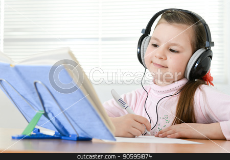 Cute schoolgirl sitting at table and doing homework stock photo, Cute schoolgirl sitting at table and doing homework at home by Ruslan Huzau