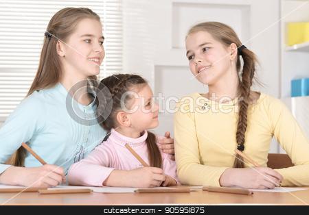 beautiful  girls doing homework stock photo, Portrait of beautiful girls doing homework at table by Ruslan Huzau