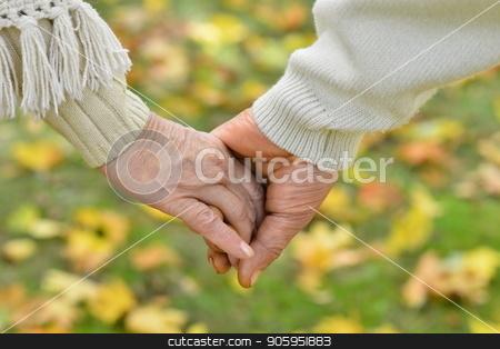 Elderly couple holding hands stock photo, Elderly couple holding hands together in autumn park by Ruslan Huzau