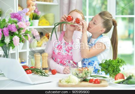Two funny girls preparing fresh salad stock photo, Two funny girls preparing fresh salad on kitchen table by Ruslan Huzau