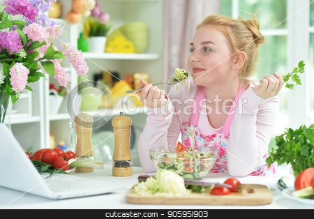 Cute teen girl using laptop stock photo, Cute teen girl using laptop while preparing fresh salad on kitchen table by Ruslan Huzau