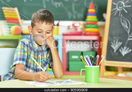 little boy drawing with pencil stock photo, Portrait of cute little boy drawing with pencils in classroom by Ruslan Huzau