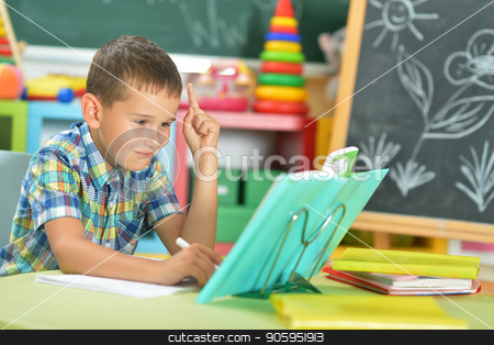 Young boy doing homework stock photo, Young boy doing homework and pointing up with finger in classroom by Ruslan Huzau