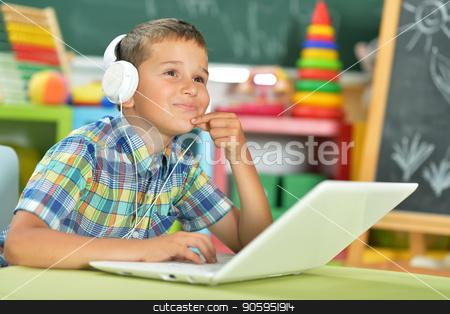 little boy using laptop  stock photo, Little boy with headphones using laptop in classroom by Ruslan Huzau