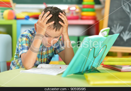 schoolboy doing homework stock photo, Portrait of tired schoolboy doing homework in classroom by Ruslan Huzau