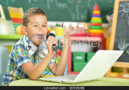 Boy singing karaoke stock photo, Portrait of boy singing karaoke with microphone and laptop by Ruslan Huzau