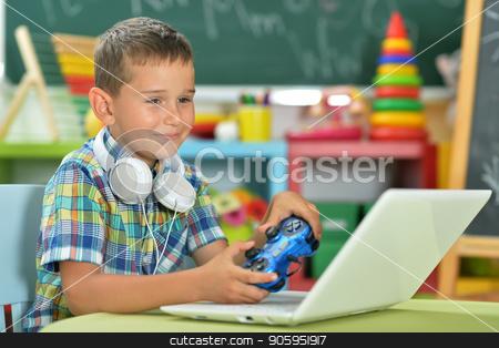little boy using laptop  stock photo, Emotional boy playing computer game with laptop by Ruslan Huzau